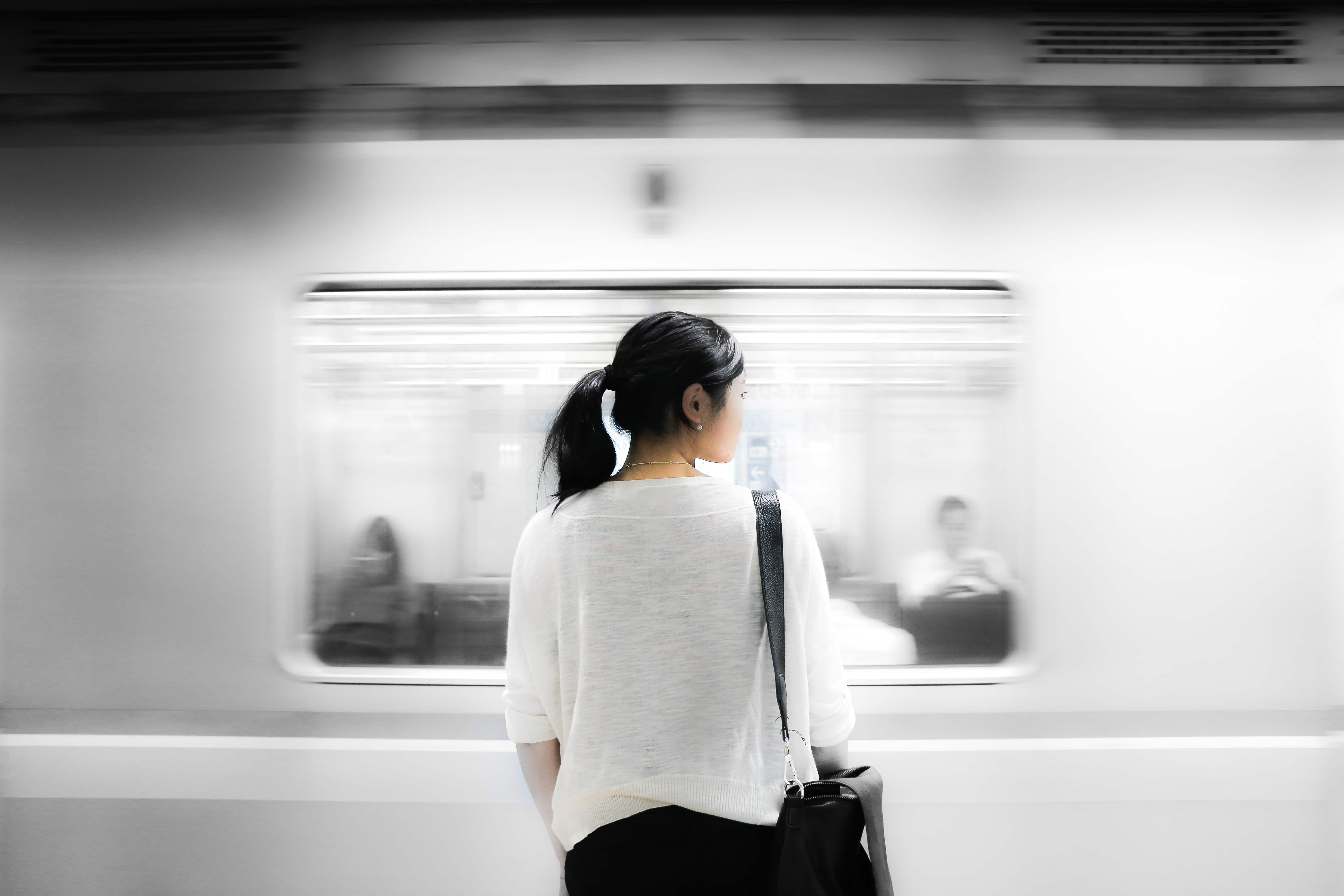 japanese woman waiting for the train and learning how to prepare for a trip to japan
