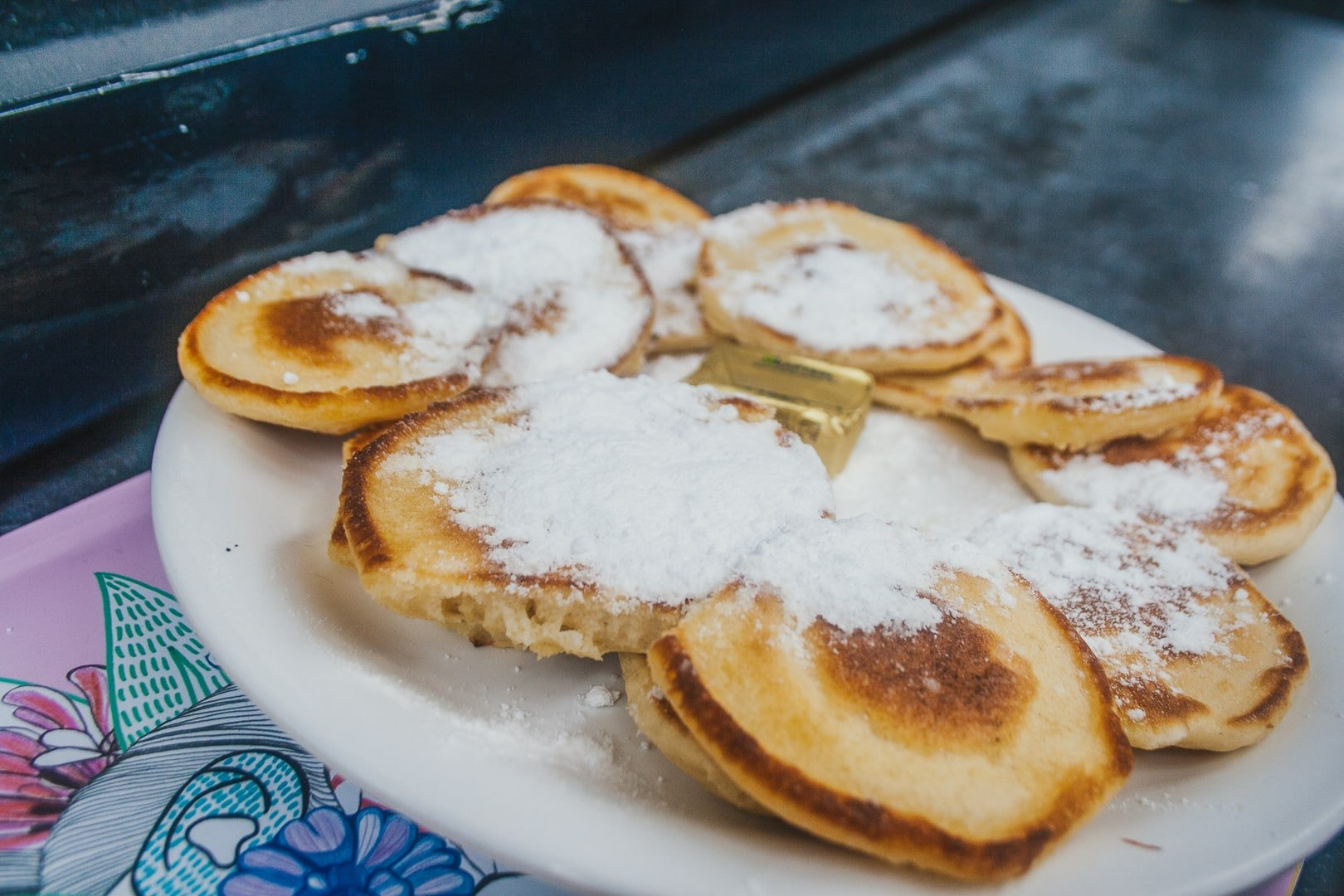 Dutch Pancakes with powdered sugar and butter, placed neatly on a white plate.