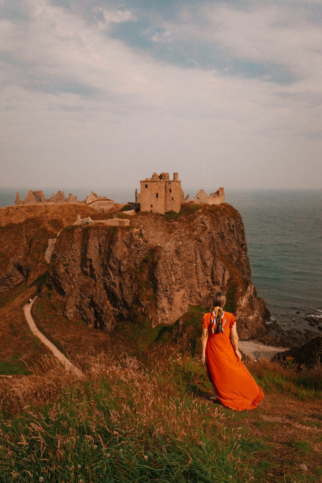 girl at dunnottar castle in scotland united kingdom, best places for landscape photography in scotland