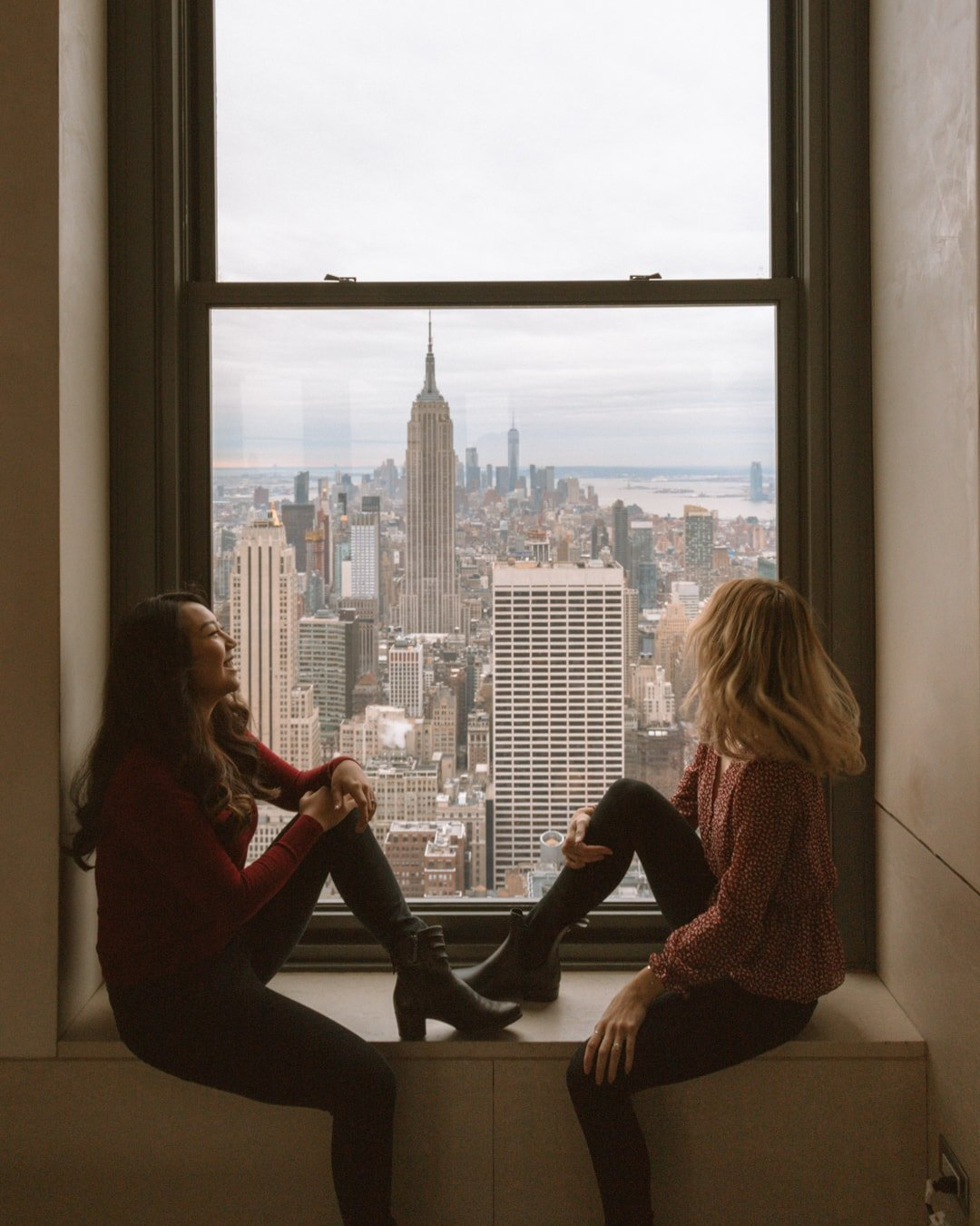 two girls looking out the window of rockefeller center