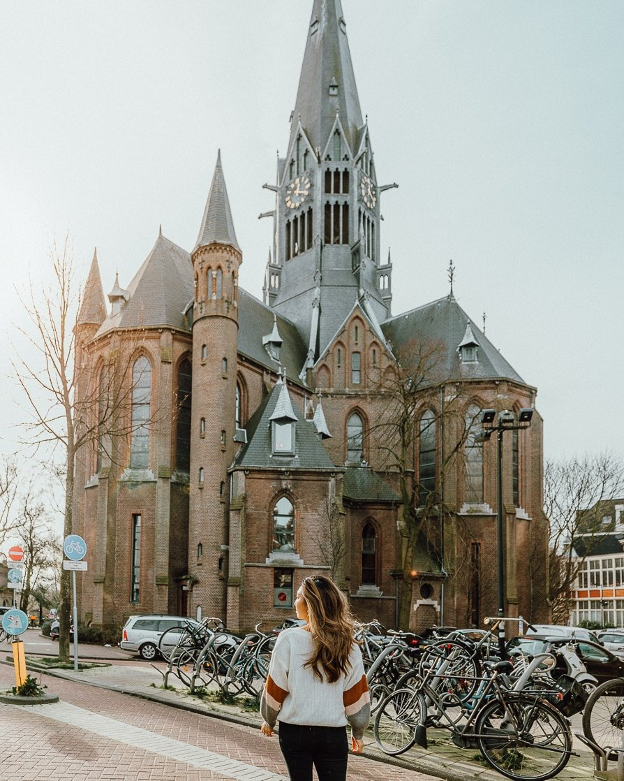 Church in Amsterdam with woman in front taking a photo