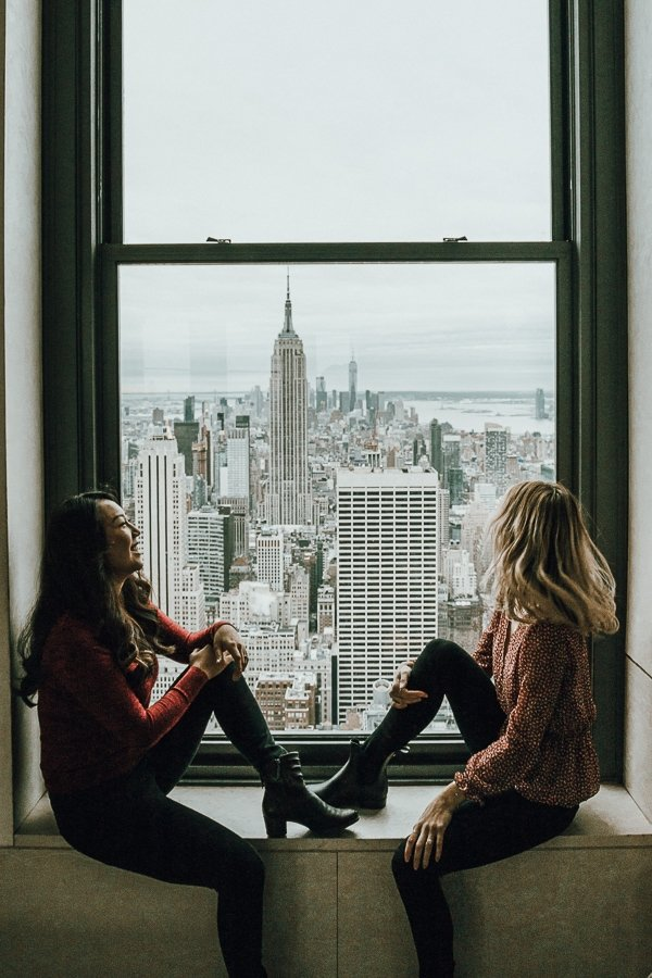 two woman overlooking manhattan from the window at top of the rock, one of the most instagrammable places in nyc